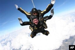FILE - Former President George H.W. Bush during free fall with U.S. Army Golden Knights parachute team member, Sgt. 1st Class Mike Elliott, College Station, Texas, Nov. 2007.