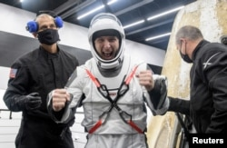 NASA astronaut Mike Hopkins is helped out of the SpaceX Crew Dragon Resilience spacecraft onboard the SpaceX GO Navigator recovery ship after he, NASA astronauts Shannon Walker, Victor Glover and Japan Aerospace Exploration Agency astronauts...