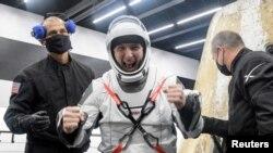 Астронавту НАСА Майку Хопкинсу помогают выбраться из капсулы SpaceX Crew Dragon Resilience после возвращения на Землю с МКС, 2 мая 2021 г. (REUTERS)