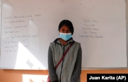 Abelina Choque stands inside her classroom next to her work, left, she wrote out on a dry erase board, during an Uru language lesson, in the Urus del Lago Poopo indigenous community, in Punaca, Bolivia, Monday, May 24, 2021.