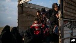 Mujeres y niños salen de un camión parte de un convoy de cientos de personas que están evacuando el último bastión de ISIS en Baghouz, este de Siria, el viernes, 22 de febrero de 2019.