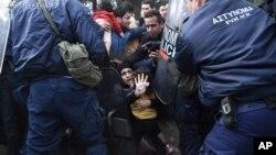 Žena pokušava da zaštiti ćerku tokom sukoba sa grčkom policijom u blizini granice sa Makedonijom, 22. novembar 2015.