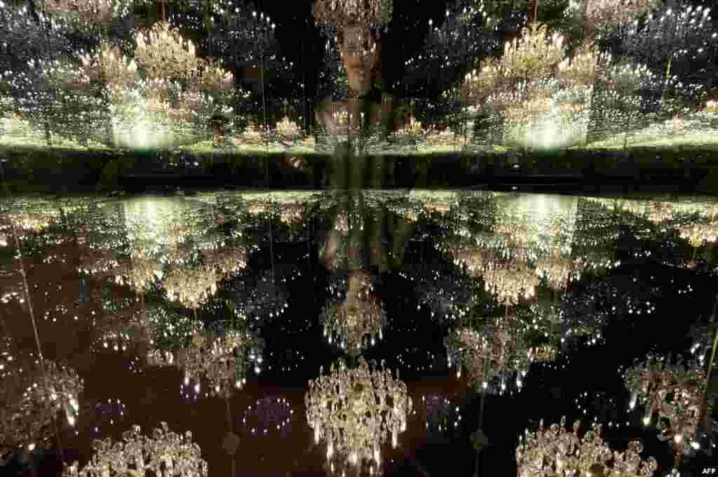 ជំនួយការក្នុងសាលសិល្បៈឈរថតរូបជាមួយនឹងការតាំងពិព័រណ៌សិល្បៈដែលមានឈ្មោះថា «Chandelier of Grief» រៀបចំដោយសិល្បករជប៉ុន Yayoi Kusama នៅឯសាលសិល្បៈ Victoria Miro ក្នុងក្រុងឡុងដ៍។