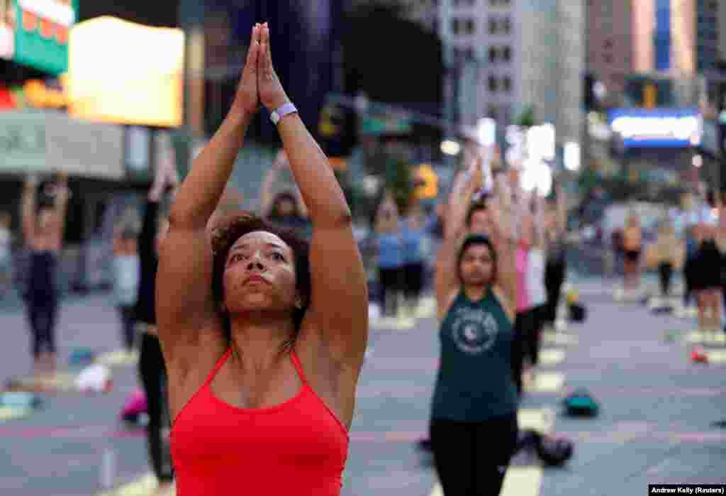 """Pessoas participam no evento de celebração do solstício na Times Square em Nova Iorque (""""Solstice in Times Square: Mind Over Madness Yoga""""). 20 de Junho, 2021"""