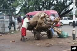 FILE: A man prepares to transport manikins to a market shop in downtown Harare, in this Monday, Dec.10 , 2018 photo.