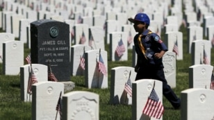 """A member of the Boy Scouts of America runs through graves while placing U.S. flags at Cypress Hills National Cemetery in Brooklyn, New York May 23, 2015. The annual """"Flags-In"""" ceremony is held ahead of Memorial Day to honor the nation's fallen members of"""