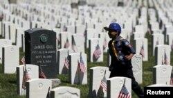 Một hướng đạo sinh Mỹ đặt cắm các lá quốc kỳ Mỹ tại các ngôi mộ trong nghĩa trang Quốc gia Cypress Hills, ở Brooklyn, New York, 23/5/15