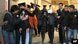 Law Wan-tung (44 tahun), menutupi wajahnya saat meninggalkan pengadilan Hong Kong (Foto: dok). Pengadilan Hong Kong memvonisnya dengan hukuman penjara enam tahun, Jumat (27/2), atas kasus penyiksaan pembantunya, Erwiana Sulistyaningsih.