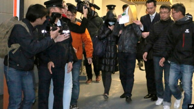 FILE - Law Wan-tung, a 44-year-old woman accused of torturing her Indonesian maid as well as two other former domestic helpers (center l) leaves a court in Hong Kong,
