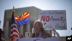 Noqonuniy muhojirlarga qarshi qabul qilingan Arizona qonunini yoqlovchi va unga qarshi bo'lganlar Oliy Sud binosi oldida namoyishga chiqishdi. 25-aprel, 2012-yil.