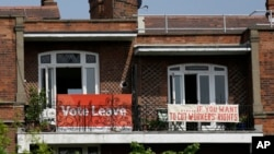 FILE - Banners of opposing views on Britain's so-called Brexit referendum on EU membership are displayed on the balconies of two neighboring apartments in the Gospel Oak area of north London, May 27, 2016.