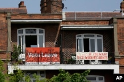 FILE - Banners of opposing views on Britain's so-called Brexit referendum on EU membership are displayed on the balconies of two neighboring apartments in the Gospel Oak area of north London, May 27, 2016. British voters will decide on June 23 on whether