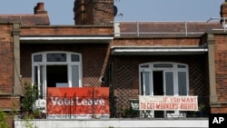 FILE - Banners of opposing views on Britain's so-called Brexit referendum on EU membership are displayed on the balconies of two neighboring apartments near London, May 27, 2016. British voters will decide on June 23 on whether to leave the bloc.