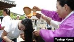 서울 시가 중국여행사총사유한공사(CTS)와 공동 개발한 '서울단오' 상품으로 입국한 중국관광객이 9일 서울 남산골한옥마을에서 창포물로 머리를 감고 있다.