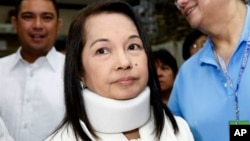 FILE - Former Philippine President and now Congresswoman Gloria Macapagal Arroyo, center, arrives at a Pasay City Court for her arraignment on electoral fraud charges in Manila, Feb. 23, 2012.