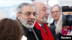 Bộ trưởng Thông tin Syria Omran Zoabi (L) nói chuyện với một nhà báo khi ông đến để dự cuộc họp với Đặc sứ Lakhdar Brahimi ở Geneve, 24/1/14