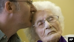 Besse Cooper receives a kiss from her grandson during a Guinness World Records ceremony in Monroe, Ga, March 10, 2011.
