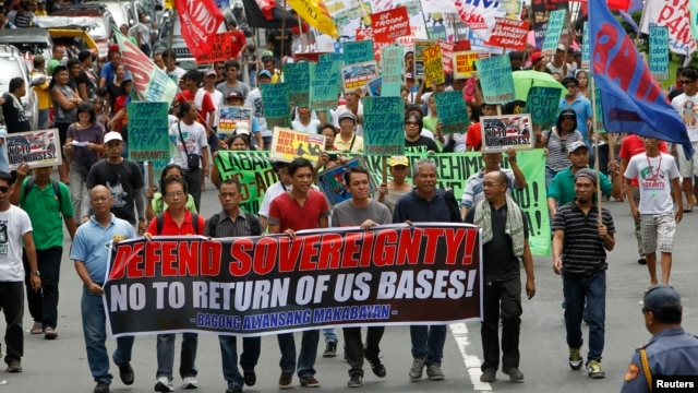 Protesters display placards and banners as they march towards the gates of the U.S. Embassy during a protest in Manila, July 4, 2013.