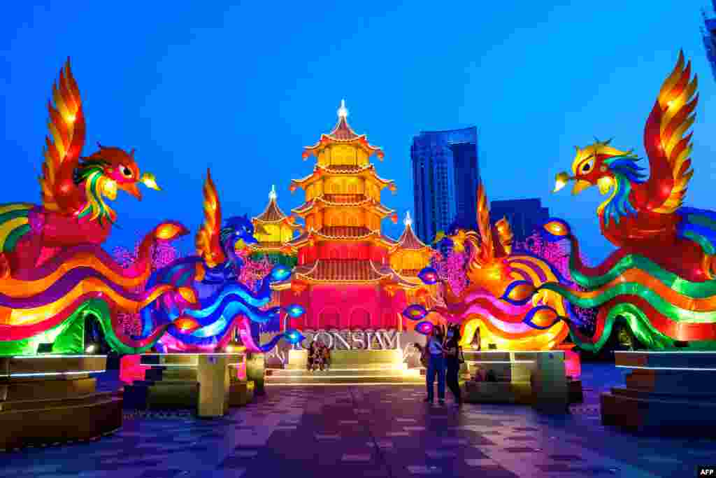 People visit a celebratory installation of pagodas and imaginary animals put in place outside a shopping mall to celebrate the upcoming Lunar New Year in Bangkok, Thailand.