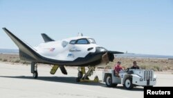 FILE - Sierra Nevada Corporation engineers and technicians prepare the firm's Dream Chaser engineering test vehicle for tow tests on a taxiway at NASA's Dryden Flight Research Center in Palmdale, California, June 27, 2013.