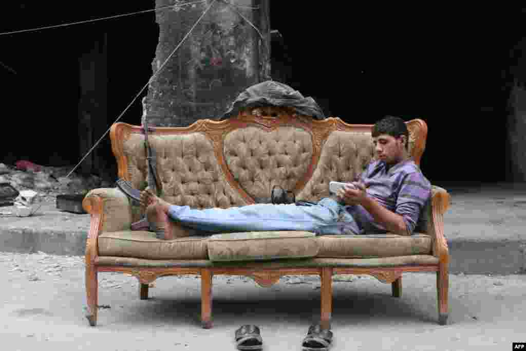 A rebel fighter looks at his smartphone lying on a sofa in Bustan Pasha neighborhood of Syria's northern city of Aleppo.