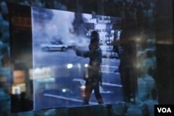 活化廳播放當年碧街騷亂電視新聞報道,有防暴警察發射催淚彈驅散示威者(美國之音湯惠芸)