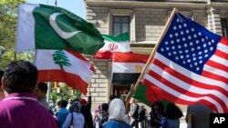 Para peserta pawai Hari Muslim di Madison Avenue, New York, membawa bendera dari berbagai negara, di antaranya Pakistan, Lebanon, Mesir dan bendera Amerika, 25 September 2016. (Foto: dok).