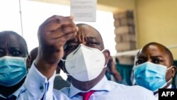 Zimbabwe vice president and Minister of Health Constantino Chiwenga holds up his vaccination certificate after receiving the first shot of Sinopharm in the southern African country which received a donation of 200 000 doses of the COVID-19 vaccine from Ch