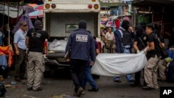Police investigators carry a body to a forensic vehicle after a shootout between private security guards and gang members at the central market in San Salvador, El Salvador, March 15, 2017. At least 30 people, mostly gang members, died in the last 24 hours in El Salvador on one of the most violent days so far this year.