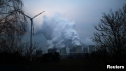 Uap air membubung dari menara-menara pendingin PLTU Jaenschwalde milik Lausitz Energie Bergbau AG, yang tak jauh dari turbin angin di Jaenschwalde, Jerman, 24 Januari 2019.