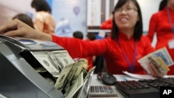 ພະນັກງານຄົນນຶ່ງຂອງທະນາຄານ Vietinbank ນັບເງິນດອລລາ ຢູ່ບ່ອນແລກປ່ຽນເງິນ ທີ່ຫໍປະຊຸມແຫ່ງຊາດ ໃນນະຄອນຫລວງຮາໂນ່ຍ ບ່ອນຈັດກອງປະຊຸມປະຈໍາປີ ທີ 44 ຂອງທະນາຄານພັດທະນາເອເຊຍ ຫລື Asian Development Bank (ADB), ເມື່ອວັນທີ 5 ພຶດສະພາ 2011.