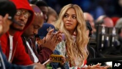 FILE - Beyonce sits at court side during the second half of the NBA All-Star basketball game in New Orleans.