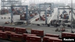 Suasana di kompleks pelabuhan kargo di Long Beach, California (4/12). Ribuan pekerja menghentikan aksi mogok dan kembali bekerja, Rabu (5/12) setelah tercapai kesepakatan sementara dengan manajemen.