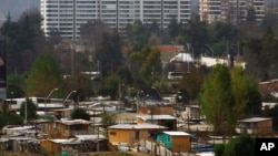 FILE - Makeshift homes fill the Vila Ermita de San Antonio neighborhood, below, near high-rise apartments located in the Las Condes sector of Santiago, Chile.
