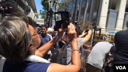 "People take ""selfies"" in front of the Erawan Shrine, location of a bomb blast in central Bangkok, Thailand, Aug. 18, 2015. (Photo: Steve Herman / VOA)"