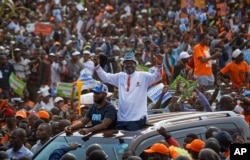 Main opposition leader Raila Odinga greets the crowd as he arrives for his final electoral campaign rally at Uhuru Park in Nairobi, Aug. 5, 2017.