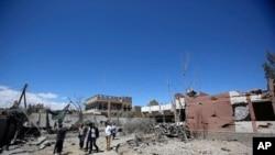 یمنی شہری صنعا میں ایک فضائی حملے سے ہونے والے نقصان کا جائزہ لے رہے ہیں۔ فائل فوٹو