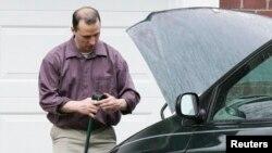 Everett Dutschke works on his mini-van in his driveway in Tupelo, Mississippi, Apr. 26, 2013.