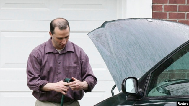 Everett Dutschke works on his mini-van in his driveway in Tupelo, Mississippi, Apr. 26, 2013.