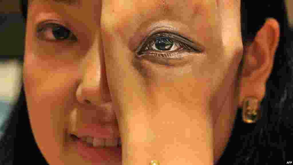 Seorang perempuan menunjukkan lukisan matanya di tangannya, hasil karya seniman Hikaru Cho dalam pameran seni di Tokyo, Jepang.