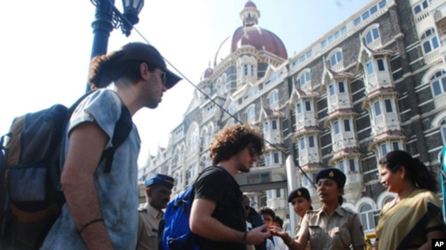Police stop foreign tourists to check their belongings at a security checkpoint outside the Taj Mahal Palace hotel in Mumbai  24 Dec, 2010. Police have launched a manhunt for four men they said belonged to a Pakistan-based militant group and had entered M