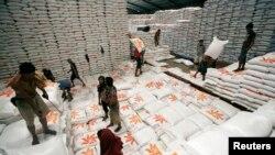 Para pekerja menurunkan karung beras dari gudang yang dimiliki oleh Bulog untuk didistribusikan ke seluruh provinsi, Jakarta 13 Mei 2011. (Foto: Reuters)