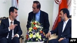 اسد (چپ) سرگرم گفت وگو با احمدی نژاد