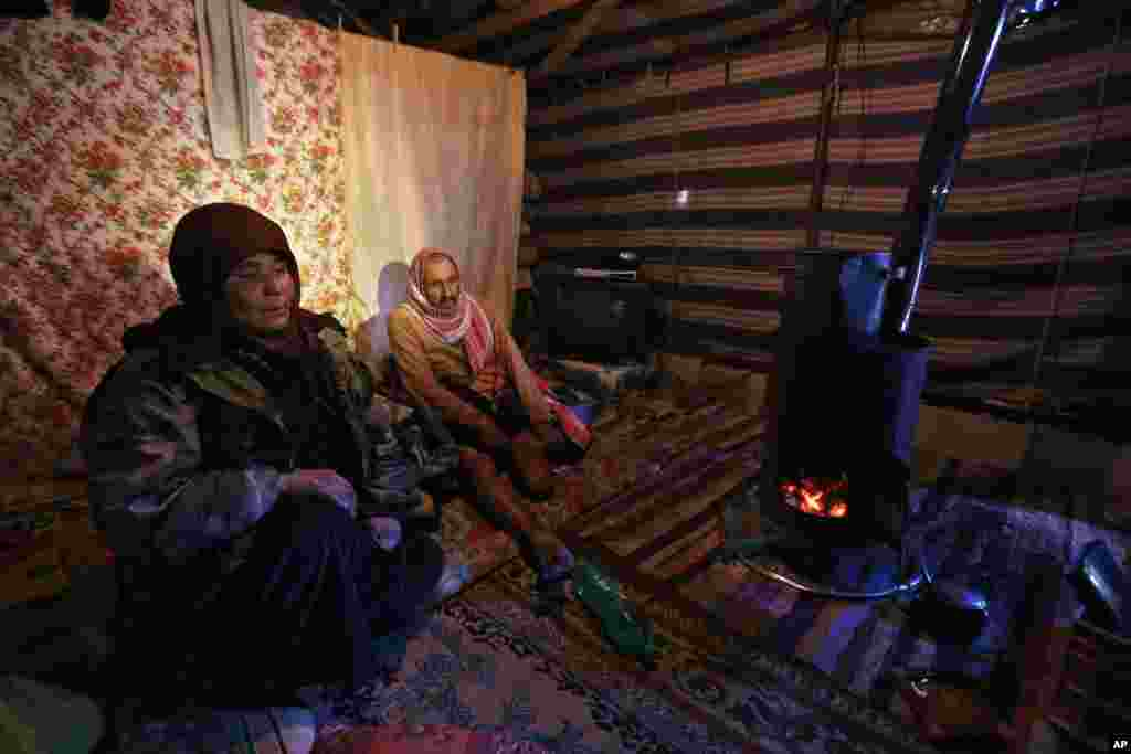 Syrian refugee Ahmed al-Hasan and his wife Mariam al-Hamed sit inside their tent at a refugee camp near the ancient Roman city of Baalbek in eastern Lebanon, Dec. 15, 2013.