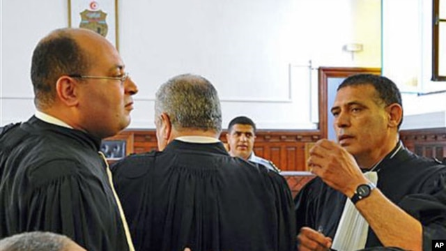 Former Tunisian President Zine El Abidine Ben Ali's lawyers Hosni Beji (L) and Abdsatar Messaoudi talk as the second trial of Tunisia's former president opened in Tunis, July 4, 2011