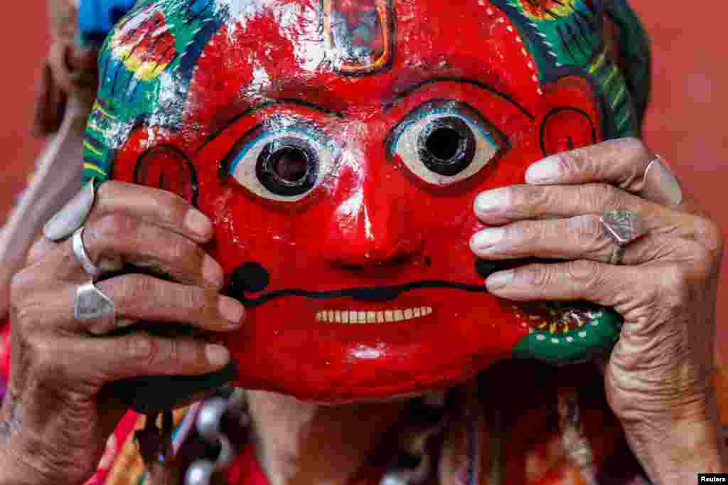 A person adjusts a clay mask while preparing to take part in a deity's procession during the Shikali festival at Khokana, in Lalitpur, Nepal.