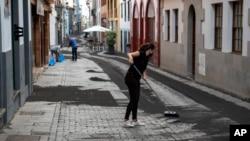 Residents clean the ash from the street in Santa Cruz de la Palma on the Canary island of La Palma, Spain, Sept. 27, 2021.