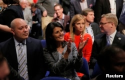 South Carolina Governor Nikki Haley applauds next to her husband, Michael, left, as she sits in the audience at the Fox Business Network Republican presidential candidates debate in North Charleston, South Carolina, Jan. 14, 2016.