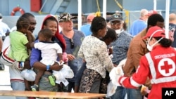 FILE - Migrants line up at a Red Cross tent after they disembarked from the Irish Navy vessel LE Niamh at the Messina harbor in Sicily, Italy, Aug. 24, 2015.