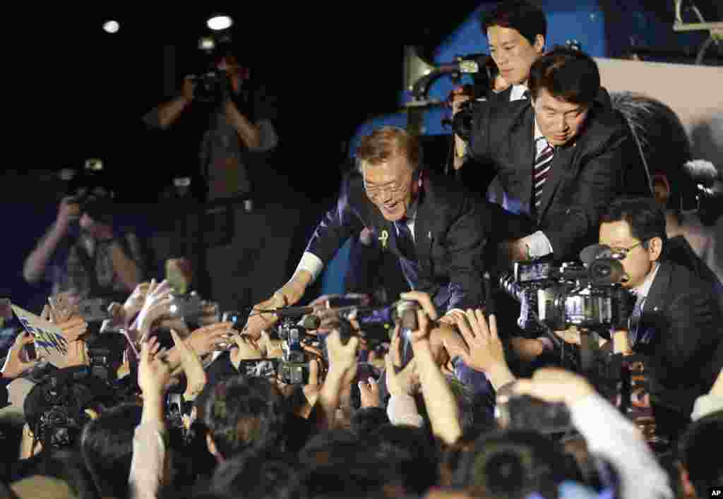 South Korea's presidential candidate Moon Jae-in of the Democratic Party is greeted by supporters as he arrives on stage to give a speech in Seoul. Moon declared victory in the country's presidential election, setting up its first liberal rule in a decade.